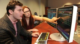 Two students at a Bloomberg Terminal. One of them is pointing something at the screen